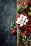 Pomodori ciliegia, foglie del basilico, formaggio della mozzarella e olio d'oliva f Immagini Stock