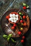 Pomodori ciliegia, foglie del basilico, formaggio della mozzarella e olio d'oliva f Immagini Stock Libere da Diritti