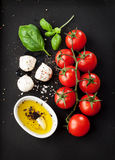 Pomodori ciliegia, formaggio della mozzarella, basilico e olio d'oliva sulla lavagna nera da sopra Immagine Stock Libera da Diritti