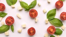 Pomodori ciliegia, formaggio e foglie verdi fresche del basilico sulla fine bianca del fondo - su con la camera mobile sulla cima stock footage