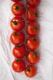 Pomodori ciliegia freschi organici sul fondo del Libro Bianco Immagine Stock