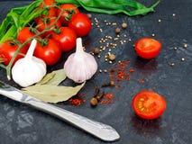 Pomodori ciliegia freschi su fondo nero con la cipolla e l'aglio Fotografia Stock
