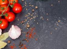 Pomodori ciliegia freschi su fondo nero con la cipolla e l'aglio Immagini Stock Libere da Diritti