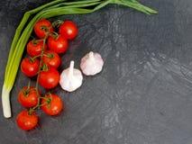 Pomodori ciliegia freschi su fondo nero con la cipolla e l'aglio Fotografia Stock Libera da Diritti