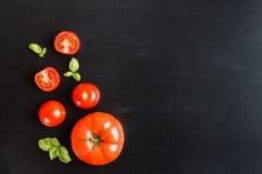 Pomodori ciliegia freschi su un fondo nero della lavagna con l'erba Immagini Stock