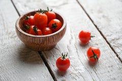 Pomodori ciliegia freschi in una ciotola sulla tavola di legno bianca fotografie stock libere da diritti