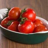 Pomodori ciliegia maturi in una ciotola su una tavola di legno Immagini Stock Libere da Diritti