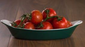 Pomodori ciliegia maturi in una ciotola su una tavola di legno Fotografie Stock Libere da Diritti