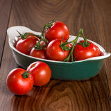 Pomodori ciliegia maturi in una ciotola su una tavola di legno Fotografia Stock Libera da Diritti