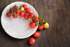 Pomodori ciliegia multicolori in piatto bianco su un fondo di legno, di alimento vegetariano, verdure Immagini Stock