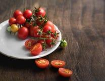 Pomodori ciliegia multicolori in piatto bianco su un fondo di legno, di alimento vegetariano, verdure Fotografia Stock Libera da Diritti