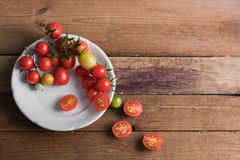 Pomodori ciliegia multicolori in piatto bianco su un fondo di legno, di alimento vegetariano, verdure Immagine Stock Libera da Diritti