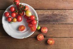Pomodori ciliegia multicolori in piatto bianco su un fondo di legno, di alimento vegetariano, verdure Fotografia Stock