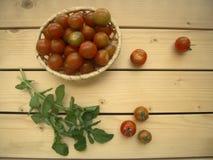 Pomodori ciliegia nel canestro e rucola su una tavola rustica fotografie stock