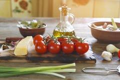 Pomodori ciliegia, olio d'oliva, aglio, ingredienti, cucina italiana fotografie stock libere da diritti