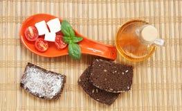 Pomodori ciliegia, pane, chees, basilico freschi e peperoncino sul piatto rosso Immagini Stock