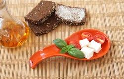 Pomodori ciliegia, pane, chees, basilico freschi e peperoncino sul piatto rosso Fotografia Stock