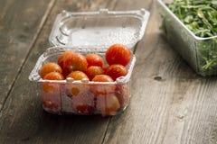 Pomodori ciliegia in piatti di plastica Fotografia Stock