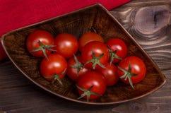 Pomodori ciliegia rossi fragranti su un ramo sul retro bordo anziano Fotografia Stock