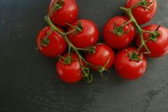Pomodori ciliegia rossi su un'ardesia Immagine Stock Libera da Diritti
