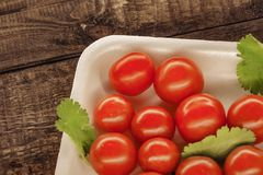 pomodori ciliegia rossi su un piatto bianco con un fondo di legno immagini stock libere da diritti