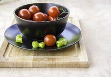 Pomodori ciliegia rossi succosi freschi e peperoncino verde Fotografia Stock