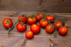Pomodori ciliegia su legno Fotografia Stock