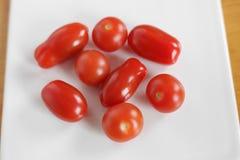 Pomodori ciliegia sul bianco ceramico Fotografia Stock