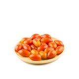 Pomodori ciliegia in tazza di legno isolata su fondo bianco Fotografie Stock Libere da Diritti