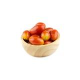Pomodori ciliegia in tazza di legno isolata su fondo bianco Immagini Stock