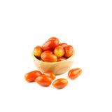 Pomodori ciliegia in tazza di legno isolata su fondo bianco Fotografia Stock
