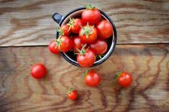 Pomodori ciliegia in tazza su una tavola di legno Immagine Stock Libera da Diritti