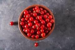 Pomodori ciliegia in una ciotola dell'argilla Fondo variopinto dei pomodori dei pomodori Fotografia Stock Libera da Diritti