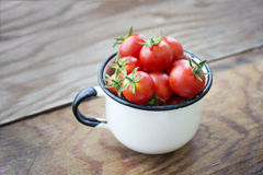 Pomodori ciliegia in una tazza d'annata sulla tavola di legno fotografie stock