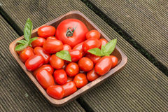 Pomodori in ciotola di legno su Floorboar Fotografie Stock