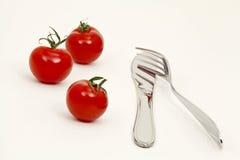Pomodori, coltello e forcella Fotografia Stock