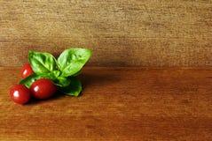 Pomodori dell'uva e un leafe di basilico su un piatto di legno in uno studio Fotografia Stock Libera da Diritti