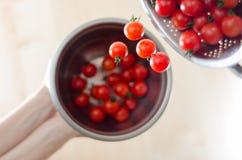 Pomodori di ciliegia che cadono dal Colander del metallo Immagini Stock Libere da Diritti