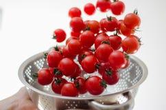 Pomodori di ciliegia che cadono nel Colander del metallo Fotografie Stock