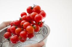 Pomodori di ciliegia che cadono nel Colander del metallo Immagini Stock