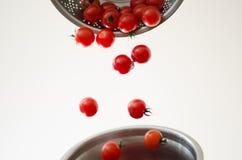 Pomodori di ciliegia che cadono nel Colander del metallo Fotografia Stock Libera da Diritti