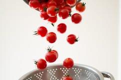 Pomodori di ciliegia che cadono nel Colander del metallo Fotografia Stock