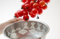 Pomodori di ciliegia che cadono nel Colander del metallo Immagine Stock