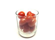 Pomodori di ciliegia isolati su priorità bassa bianca Immagine Stock