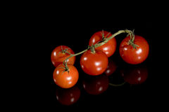 Pomodori di ciliegia rossi isolati sul nero Fotografia Stock