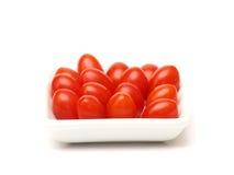 Pomodori di ciliegia su una zolla bianca Fotografia Stock