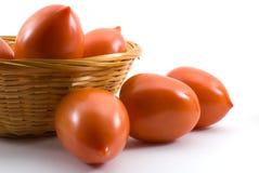 Pomodori di prugna isolati su una priorità bassa bianca fotografia stock