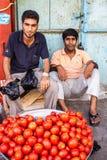 Pomodori di vendita degli uomini fotografia stock