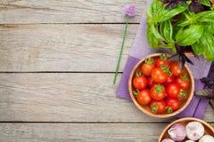 Pomodori e basilico freschi degli agricoltori sulla tavola di legno Fotografia Stock