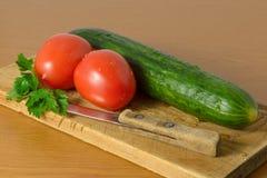 Pomodori e cetrioli sulla scheda di taglio Fotografia Stock Libera da Diritti